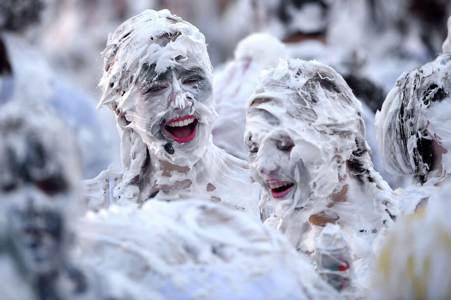 Students from St Andrew's University indulge in a tradition of covering themselves with foam to honour the 'academic family' on November 4, 2013, in St Andrews, Scotland. Every November the 'raisin weekend' which is held in the university's St Salvator's Quadrangle, is celebrated and a gift of raisins (now foam) is traditionally given by first year students to their elders as a thank you for their guidance and in exchange they receive a receipt in Latin. Photo: Jeff J Mitchell, Getty Images / 2013 Getty Images
