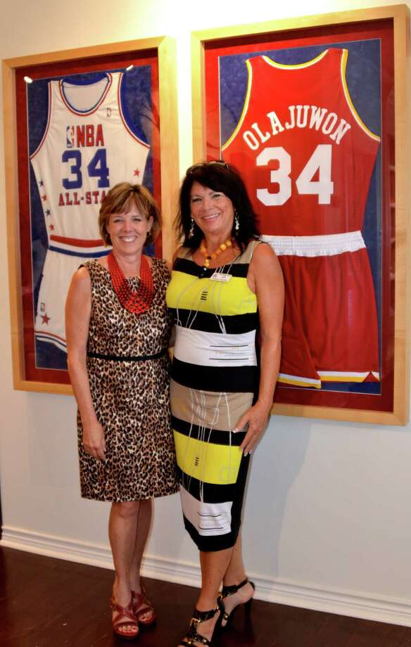 Assistance League of the Bay Area Gala Vice Chairwoman Dee Cover and Chairwoman Kathleen Courville stand in front of Hakeem Olajuwon's framed uniforms at the historic West Mansion that is now his private design house DR34M. Photo: Courtesy Of Assistance League Of The Bay Area