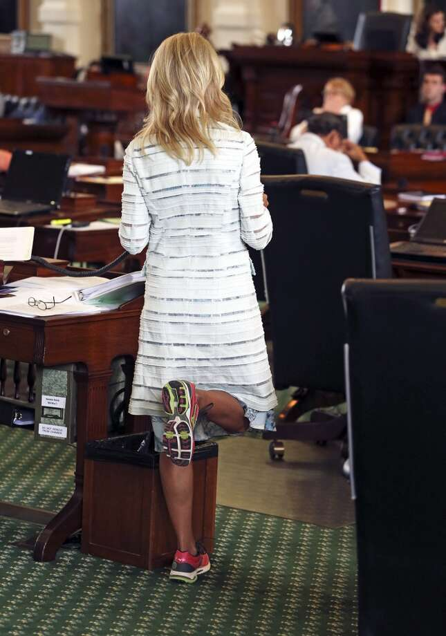 Fort Worth Senator Wendy Davis relieves pressure on her feet as she filibusters in an effort to cause abortion legislation to die without a vote on the floor of the Senate Tuesday, June 25, 2013. Photo: TOM REEL, San Antonio Express-News