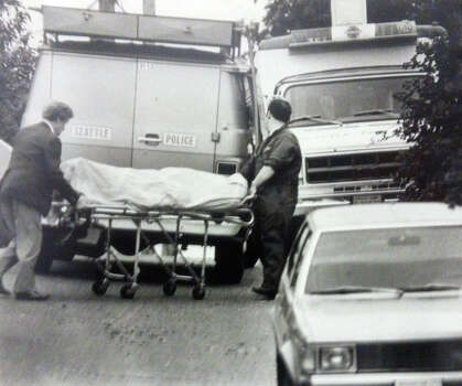 Investigators move the body of a woman found slain. Photo filed July 11, 1983. (Photo by Kurt Smith, copyright MOHAI, Seattle Post-Intelligencer Collection, 2000.107) Photo: MOHAI Archive