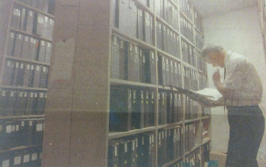 King County police Detective Jim Doyon scans the column of files on the Green River killer stored at the King County Courthouse. Photo filed 1990. (Photo by Mike Bainter, copyright MOHAI, Seattle Post-Intelligencer Collection, 2000.107) Photo: MOHAI Archive