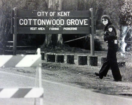 "A City of Kent police officer watches over a barracaded and taped off area in Cottonwood Grove on Frager Road on the Green River. ""Possible human remains"" were found there by a passerby. (Copyright MOHAI, Seattle Post-Intelligencer Collection, 2000.107) Photo: MOHAI Archive"