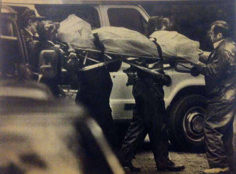 Green River Task Force officers carried a woman's shrouded body from a wooded area near Kapowsin in Pierce County. She could well be the 27th victim of the Green River serial killer. Photo filed Sept. 15, 1984. (Copyright MOHAI, Seattle Post-Intelligencer Collection, 2000.107) Photo: MOHAI Archive