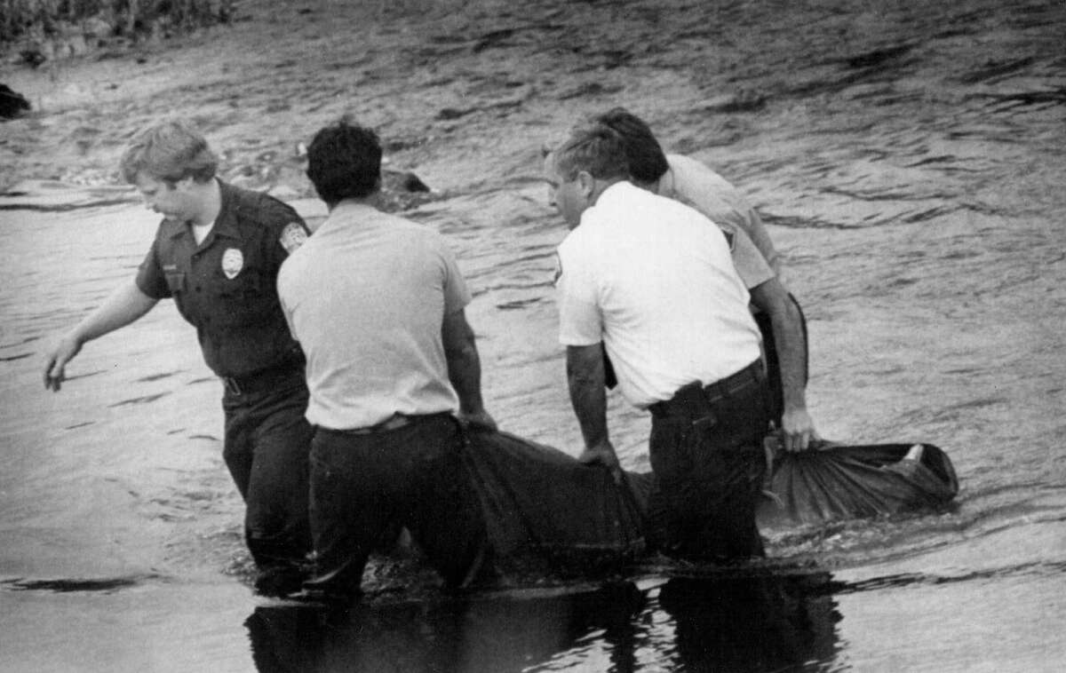 Officials remove the body of 16-year-old Wendy Lee Coffield from the Green River on July 15, 1982. The discovery of the body behind a meat packing plant was the first clue police had to the developing nightmare of the Green River serieal killer's actions. Photo filed July 15, 1982. (Copyright MOHAI, Seattle Post-Intelligencer Collection, 2000.107)