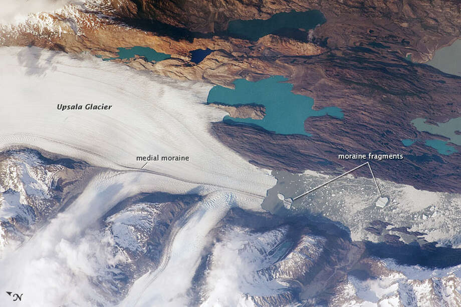 The Southern Patagonian Icefield of Argentina and Chile is the southern remnant of the Patagonia Ice Sheet that covered the southern Andes Mountains during the last ice age. This detailed astronaut photograph from October 2009 illustrates the terminus of one of the icefield's many spectacular glaciers—Upsala Glacier, located on the eastern side of the icefield. Upsala is the third largest glacier in the icefield, and like most other glaciers in the region, it has experienced significant retreat over the past century. This image was taken during spring in the Southern Hemisphere, and icebergs were calving from the glacier terminus into the waters of Lago Argentino (Lake Argentina, image right). Two icebergs are especially interesting because they retain fragments of the moraine (rock debris) that forms a dark line along the upper surface of the glacier. Photo: NASA
