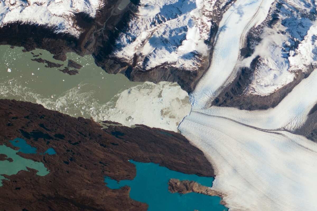 This image shot from the International Space Station shows the snout of the Upsala Glacier (49.88°S, 73.3°W) on the Argentine side of the North Patagonian Icefield. Ice flow in this glacier comes from the north (right in this rotated image). Dark lines of rocky debris (moraine) within the ice give a sense of the slow ice flow from right to left. The water color in Lago Argentino is related to the glacier flow. The lake receives most of the ice from the glacier and thus receives most of the