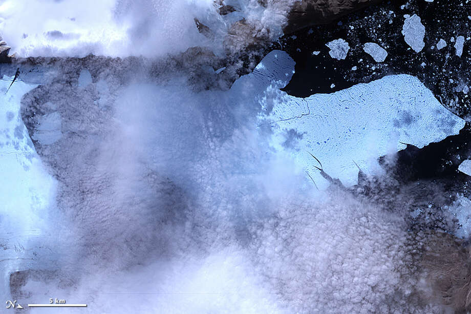 After breaking off the Petermann Glacier on August 5, 2010, a massive ice island floated slowly down the fjord toward the Nares Strait. The Advanced Spaceborne Thermal Emission and Reflection Radiometer (ASTER) on NASA's Terra satellite captured this false-color image of the ice island on August 11, 2010. In this image, ice is light blue, water is nearly black, and clouds are nearly white. Although a bank of thin clouds hovers over the fjord, the southernmost margin of the ice island is still visible. Toward the north, the leading edge of the ice island retains the same shape it had days earlier, at the time of the initial calving. Photo: NASA