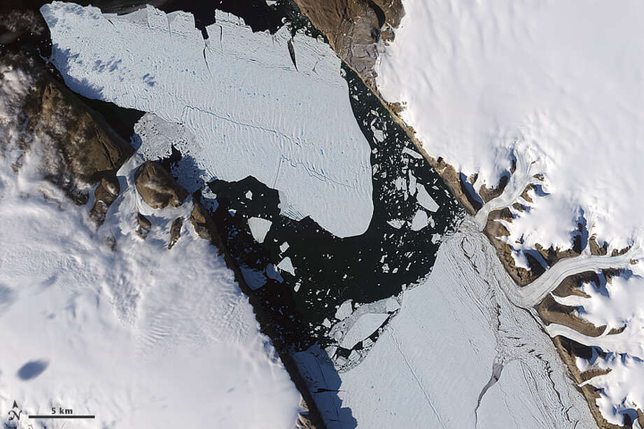 The ice island that calved off the Petermann Glacier in northwestern Greenland on August 5, 2010, was continuing its slow migration down the fjord 11 days later. Photo: NASA
