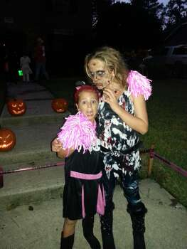 My 11 yr old daughter Maddie dressed as a Zombie rock star and my 6 yr old daughter Camie as a cheerleader, who is scared at the moment!