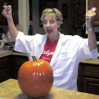 "Ann Bolton is dressed in a Walgreen's T-shirt and Wal-mart pharmacy jacket. Photo by Michael Bolton. ""Pumpkins must have flu shots"" is based on all the promotions for having a flu shot plus the fact that Pharmacists are being trained and tested to give flu shots. The Wally Effect of flu shots is Wal times two (Walgreen's and Wal-mart).