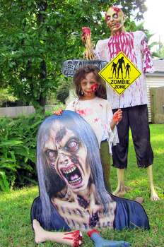 "My family loves to decorate our yard for Halloween. We get a lot of trick-or-treaters who return year after year. It brings us a lot of joy to see others share in our Halloween spirit and decorations. This is a picture of our ""Zombie Feeding Area"". If you look closely, you may be able to pick out the ""human"" zombie, my daughter, Lydia. She wanted to be a zombie this year, so her big sister, Amelia, who is an artist and a fan of the Walking Dead,did her make-up.
