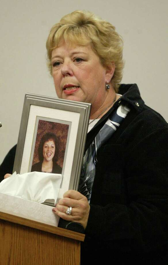 Merti Winston holds a photo of her daughter Tracy Winston as she speaks at the sentencing of Gary Ridgway in King County Washington Superior Court December 18, 2003 in Seattle, Washington. Ridgway received 48 life sentences, without the possibility of parole, for killing 48 women over the past 20 years in the Green River Killer serial murder case. Photo: Pool, / / 2003 Getty Images