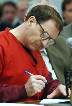 Gary Ridgway signs papers signifying that he is pleading guilty to 48 counts of aggravated first degree murder in the Green River killing cases, in front of Judge Richard A. Jones Wednesday, Nov. 5, 2003, in Seattle. The King County agreement, signed June 13, puts more murders on his record than any other serial killer in U.S. history. (AP Photo/Elaine Thompson ) Photo: ELAINE THOMPSON, P-I File Photos / AP POOL