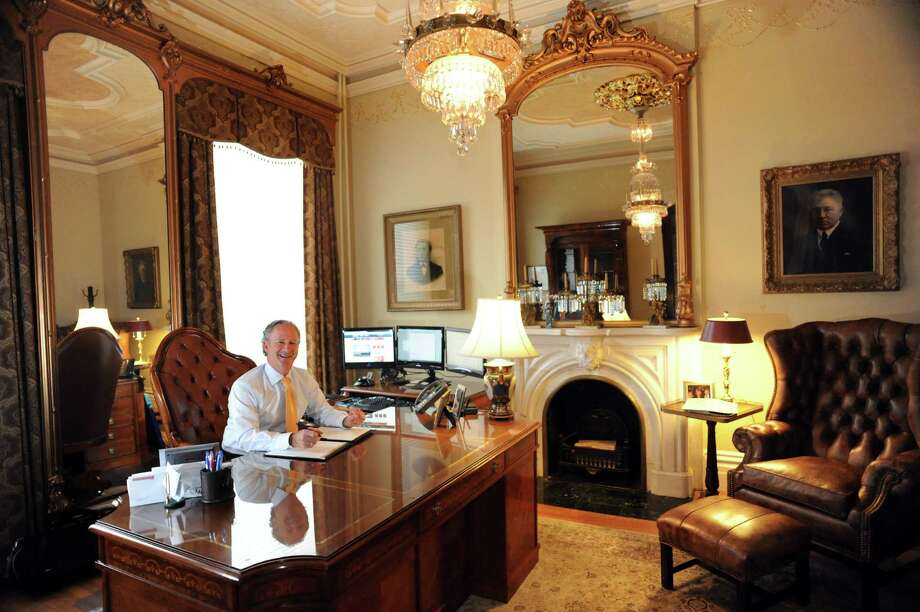 A portrait  from of the home's first resident, Sen. Edward Murphy, hangs to the left of the fireplace in Steven Bouchey's office. The portrait to the right is of Cornelius Burns, a five-term Troy mayor. Bouchey said he wasn't expecting this kind of grandeur when he shopped for real estate in 2002. He was sold when the previous owner asked the then 45-year-old Bouchey, 'where do you want to go to work everyday for the next 20 years?' Photo: Cindy Schultz / 00024231A