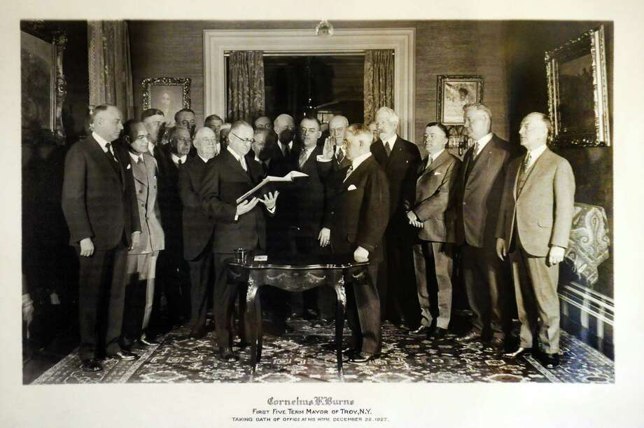 Copy of a photograph of former home-owner Cornelius R. Burns, center right, on Tuesday, Oct. 15, 2013, at Bouchey Financial Group in Troy, N.Y. In this picture, the five-term mayor of Troy was taking the oath of office in the home on Dec. 22, 1927. (Cindy Schultz / Times Union) Photo: Cindy Schultz / 00024231A
