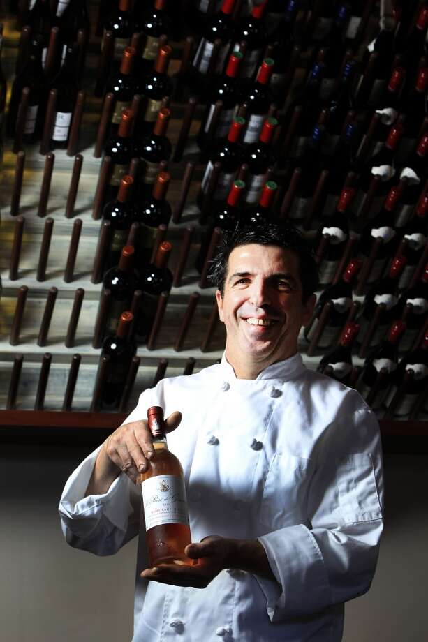 Etoile owner-chef Philippe Verpiand makes a choice from his wine menu. (Karen Warren / Houston Chronicle ) Photo: Karen Warren, Houston Chronicle