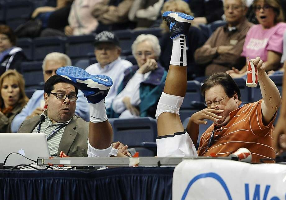 Don't you go where the Huskies go: Diving for a ball, Connecticut's Kaleena Mosqueda-Lewis lands in the laps of Hartford Courant writer John   Altavilla (left) and Associated Press freelancer Ken Davis during the second half of the UConn-Gannon game in   Storrs. Davis has the presence of mind to lift his soft drink out of harm's way. Photo: Jessica Hill, Associated Press