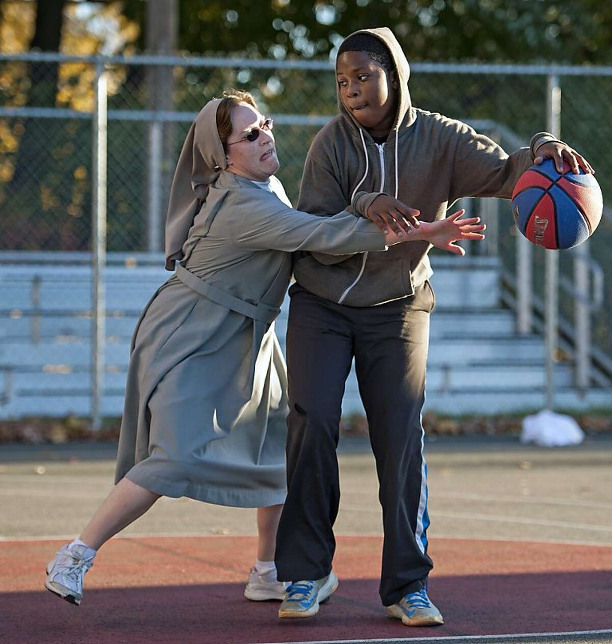 Thou shalt not steal, Sister: Thirteen-year-old Muhammah Norris tries to keep Sister Mary Jackson at arm's length during a game of one-on-nun at Mary Help of Christians Academy in North Haledon, N.J.