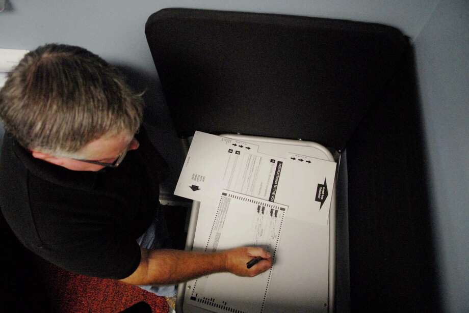Kevin O'Malley, Rensselaer County Board of Election voting machine technician,  uses a privacy booth to mark his paper ballot as he demonstrates how to use the paper ballot optical scan voting system.   (Paul Buckowski / Times Union) Photo: Paul Buckowski / 00010157A