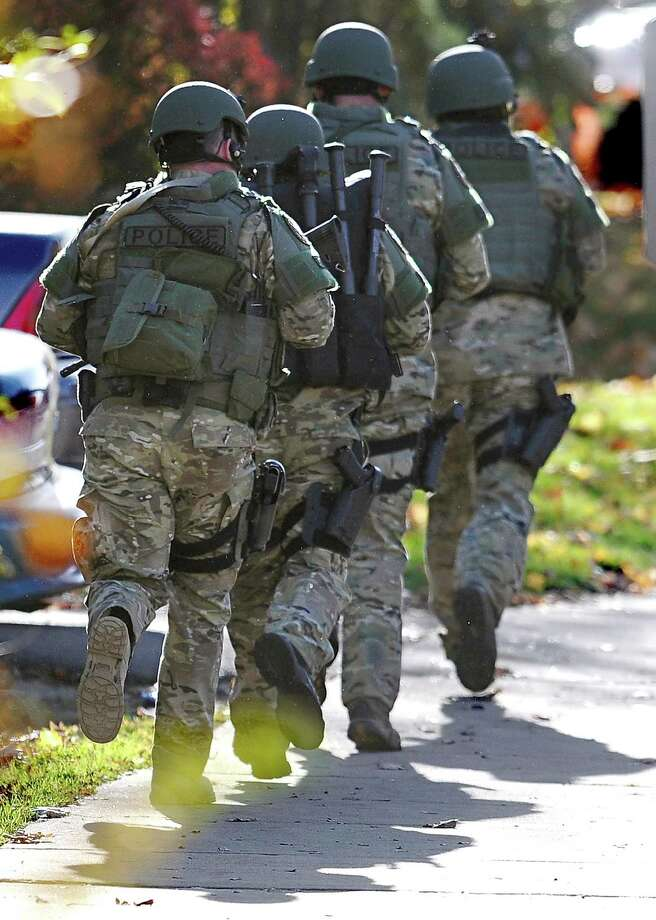 "SWAT move in a line on the campus of Central Connecticut State University, Monday, Nov. 4, 2013, in New Britain, Conn.  An armed man was spotted on the campus of Central Connecticut State University,  prompting a schoolwide lockdown and warnings for students to stay away from windows as police SWAT teams swarmed the area.  University spokesman Mark McLaughlin said, ""Somebody was seen either with a gun or was thought to have a gun."" Photo: Jessica Hill, AP Photo/Jessica Hill / Associated Press AP Photo/Jessica Hill"