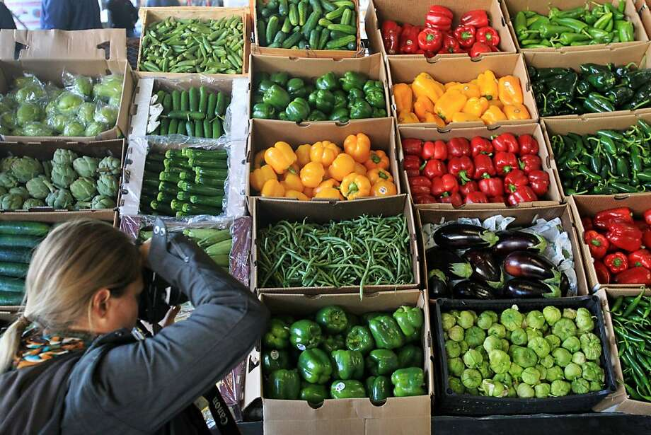 Flower seller Katie Koch photographs fruits and vegetables during a tour of Washington Vegetable Co. in San Francisco. Photo: Leah Millis, The Chronicle