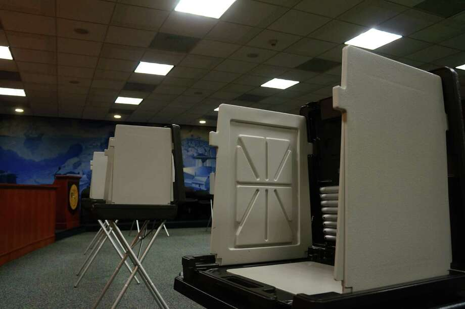 Scanners wait to record your votes for town offices. Photo: Justin Pottle, Greenwich Time / Greenwich Time