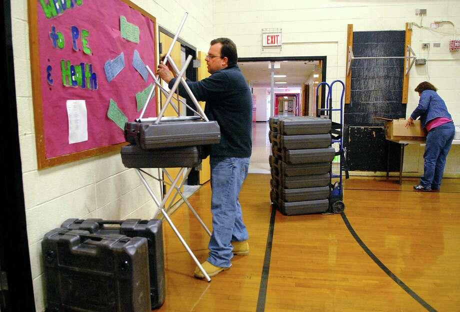 Partick Corelli and Lisa Karwoski set up voting machines at Turn of River School in Stamford, Conn. on Monday November 4, 2013. Photo: Dru Nadler / Stamford Advocate Freelance