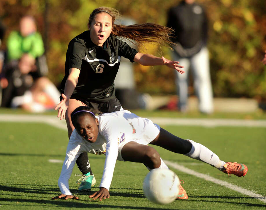 Trumbull's Kyriaki Marinos trips Westhill's Chelsea Domond during their CIAC tournament first round game at Westhill High School in Stamford, Conn., on Monday, Nov. 4, 2013. Trumbull won, 4-0. Photo: Jason Rearick / Stamford Advocate