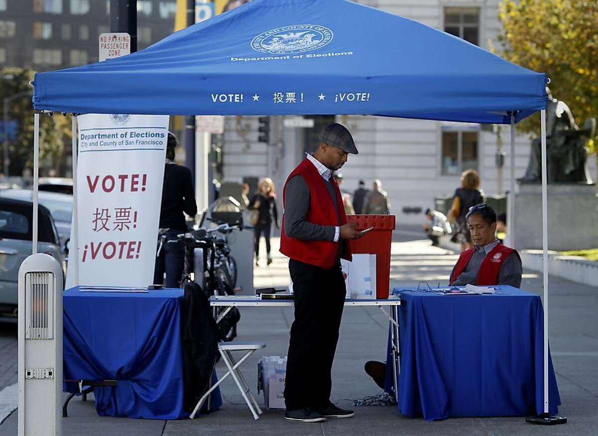 Eric Colston (left) and Alan Samatra manned the curb side drop off area on Polk Street Monday November 4, 2013 in San Francisco, Calif. Early and curb side voting at San Francisco City Hall was slow with Proposition B and C getting most of the attention on the day before election day.