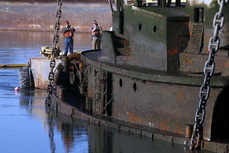 Contractors with the EPA take pictures as they raise a sunken tugboat known as Captain Al in the Oakland Estuary. Photo: Lacy Atkins, The Chronicle