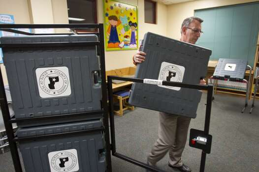 Charles Holloway, Precinct 67 alternate election judge, takes an E-Slate voting machine from a storage rack while setting up a polling place at Brookline Elementary Monday, Nov. 4, 2013, in Houston. ( Brett Coomer / Houston Chronicle ) Photo: Brett Coomer, Houston Chronicle