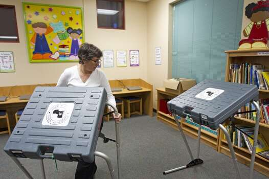 Lisi Cocina, Precinct 67 election judge, moves a voting booth into position while setting up a polling place at Brookline Elementary Monday, Nov. 4, 2013, in Houston. ( Brett Coomer / Houston Chronicle ) Photo: Brett Coomer, Houston Chronicle