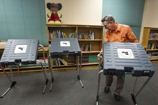 Charles Holloway, Precinct 67 alternate election judge, moves a voting booth into position while setting up a polling place at Brookline Elementary Monday, Nov. 4, 2013, in Houston. ( Brett Coomer / Houston Chronicle ) Photo: Brett Coomer, Houston Chronicle