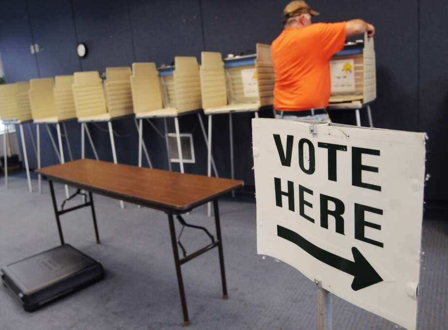 Jim Frazee, with the St. Joseph City Streets and Sanitation Department, helps set up voting booths Monday, November 4, 2013 as the city prepares for election day at the Maud Preston Palenske Memorial Library in St. Joseph, Mich. (AP Photo/The Herald-Palladium, Don Campbell) Photo: DON CAMPBELL, Associated Press
