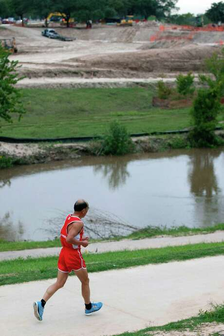 A runner jogs next to Buffalo Bayou as construction on Buffalo Bayou Park continues near Sabine Street on Monday. Photo: Johnny Hanson, Staff / Houston Chronicle