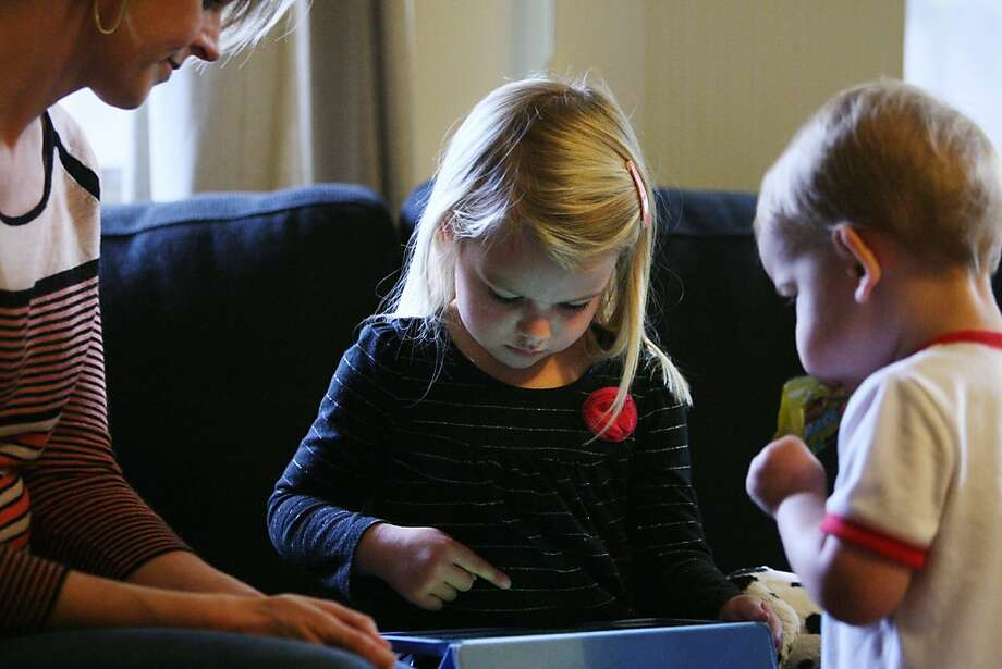 Sylvia Collins, 4, plays with an iPad while mother Janice and brother Henry watch at their home in San Rafael. Photo: Raphael Kluzniok, The Chronicle