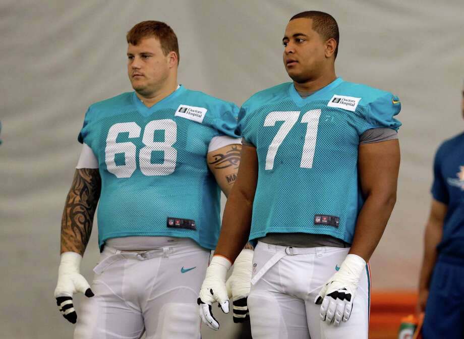 FILE - In this July 24, 2013 file photo, Miami Dolphins guard Richie Incognito (68) and tackle Jonathan Martin (71) stand on the field during an NFL football practice in Davie, Fla. Two people familiar with the situation say suspended Dolphins guard Incognito sent text messages to teammate Jonathan Martin that were racist and threatening. The people spoke to The Associated Press on condition of anonymity because the Dolphins and NFL haven't disclosed the nature of the misconduct that led to Incognito's suspension. Martin remained absent from practice Monday, Nov. 4, 2013, one week after he suddenly left the team.  (AP Photo/Lynne Sladky, File) ORG XMIT: NY167 Photo: Lynne Sladky / AP