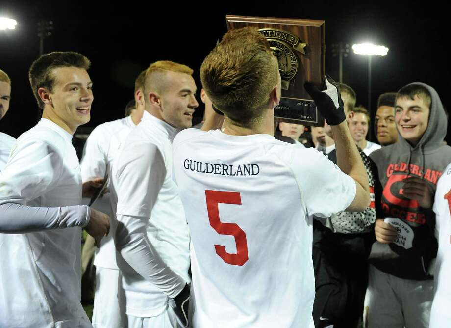 Guilderland's Connor O'Brien kisses the championship plaque as the team celebrates a win against Albany at the end of the Section II Class AA boys' soccer final on Monday, Nov. 4, 2013 in Colonie, N.Y.  (Lori Van Buren / Times Union) Photo: Lori Van Buren / 00024503A