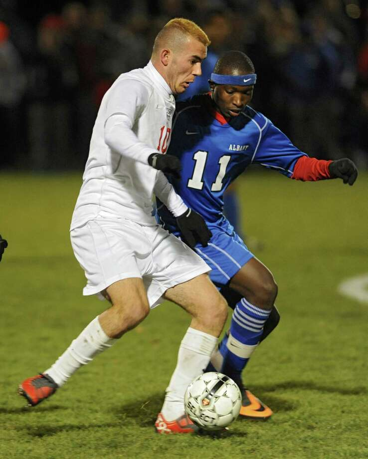 Guilderland's Kledis Capollari, left, and Albany's Erick Kwizera battle for the ball during the Section II Class AA boys' soccer final on Monday, Nov. 4, 2013 in Colonie, N.Y.  (Lori Van Buren / Times Union) Photo: Lori Van Buren / 00024503A