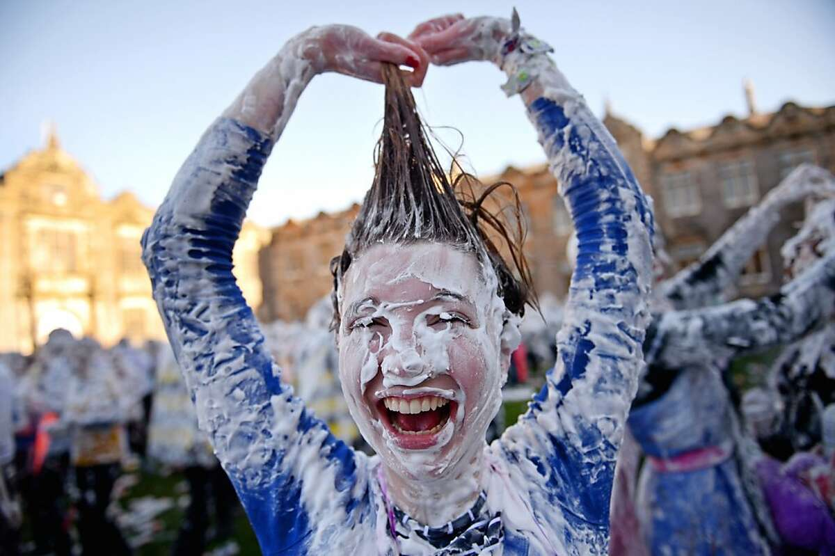 ST ANDREWS, SCOTLAND - NOVEMBER 04: Students from St Andrew's University indulge in a tradition of covering themselves with foam to honour the 'academic family' on November 4, 2013, in St Andrews, Scotland. Every November the 'raisin weekend' which is held in the university's St Salvator's Quadrangle, is celebrated and a gift of raisins (now foam) is traditionally given by first year students to their elders as a thank you for their guidance and in exchange they receive a receipt in Latin. (Photo by Jeff J Mitchell/Getty Images) *** BESTPIX ***