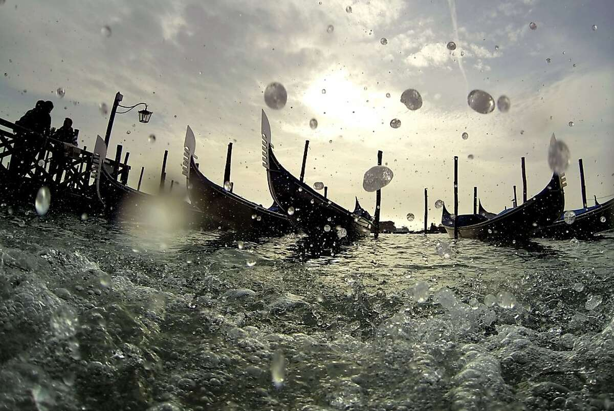 Moored gondolas are shaked by waves across the water from the Piazza San Marco (Saint Mark's Square) in Venice on November 4, 2013. TOPSHOTS/AFP PHOTO / OLIVIER MORINOLIVIER MORIN/AFP/Getty Images