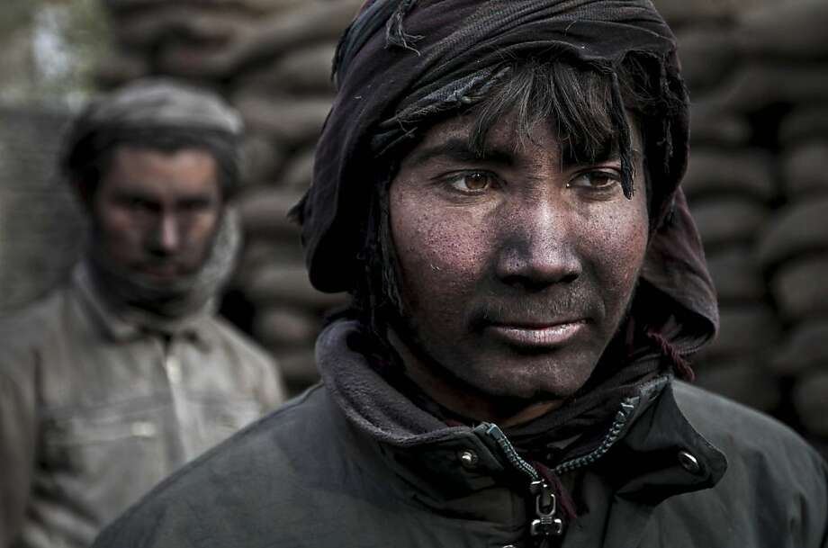 One look at his face will tell you that Qudrat, an 18-year-old who lives on the outskirts of Kabul, works at a charcoal shop. With winter approaching, the price of wood and charcoal is rising in Afghanistan. Photo: Rahmat Gul, Associated Press