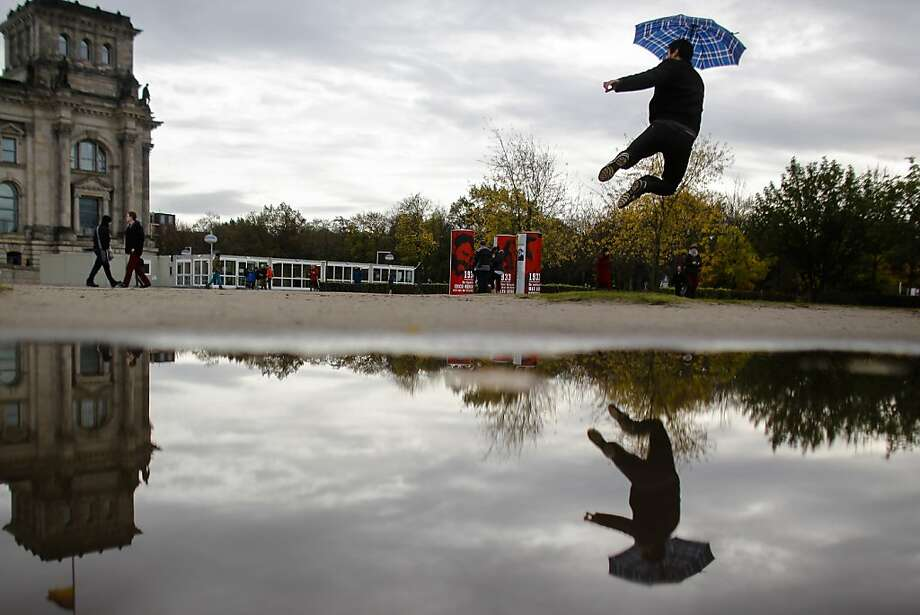 A tourist goes all Mary Poppinsto avoid a puddle on a rainy autumn day near the Reichstag building in Berlin. Photo: Markus Schreiber, Associated Press