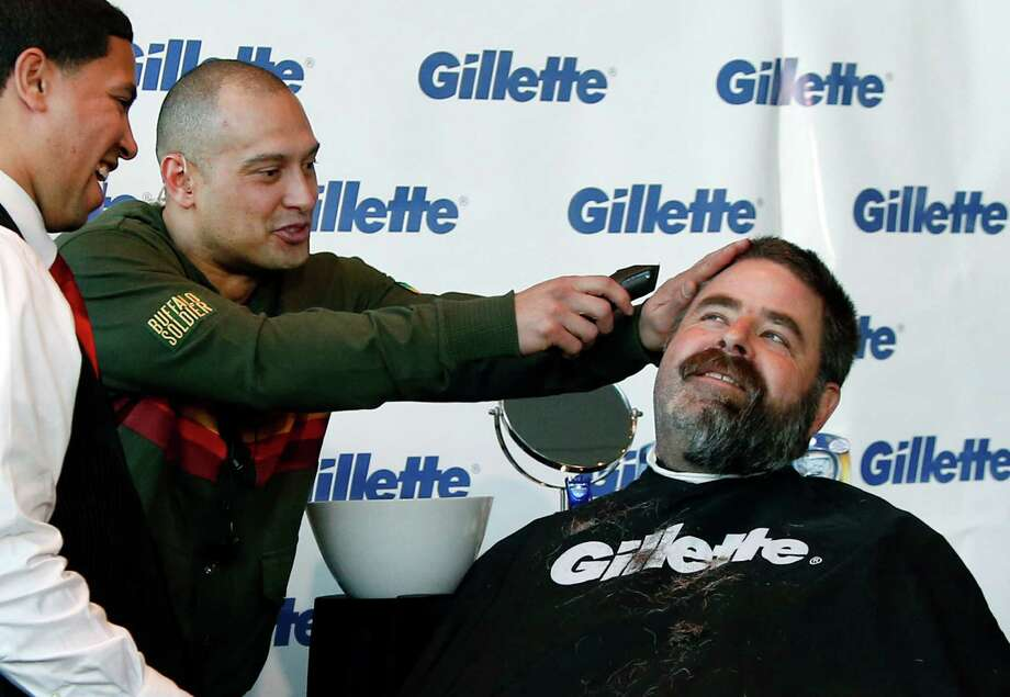 Boston Red Sox player Shane Victorino, center, kids around with a razor as Boston Police Officer Steve Horgan, right, is shaved for One Fund Boston, the Boston Marathon charity for bombing victims, during a shave-off in Boston, Monday, Nov. 4, 2013. Horgan, who was stationed in the Boston Red Sox bullpen at Fenway Park, became a city icon after he was photographed with his arms in the air celebrating Red Sox's David Ortiz's grand slam in the AL championship baseball series against Detroit. (AP Photo/Elise Amendola) ORG XMIT: MAEA107 Photo: Elise Amendola / AP