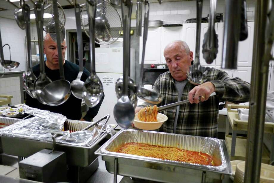 Volunteers, John Mamone, left, from Wynantskill, and Tony Carnevale from Troy dish out food in the kitchen at the  Italian Community Center during the annual pre-election day spaghetti and meatball dinner on Monday, Nov. 4, 2013, in Troy, NY.  Funds raised from the dinner are used for the center's soup kitchen, the St. Joseph's and St. Anthony's Food Pantry and the Father Harry Scholarship at LaSalle Institute.  (Paul Buckowski / Times Union) Photo: Paul Buckowski / 00024485A