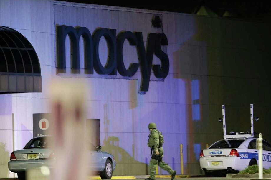 An official wearing tactical gear walks outside of Garden State Plaza Mall following reports of a shooter, Monday, Nov. 4, 2013, in Paramus, N.J. Hundreds of law enforcement officers converged on the mall Monday night after witnesses said multiple shots were fired there. Photo: Julio Cortez, AP / AP
