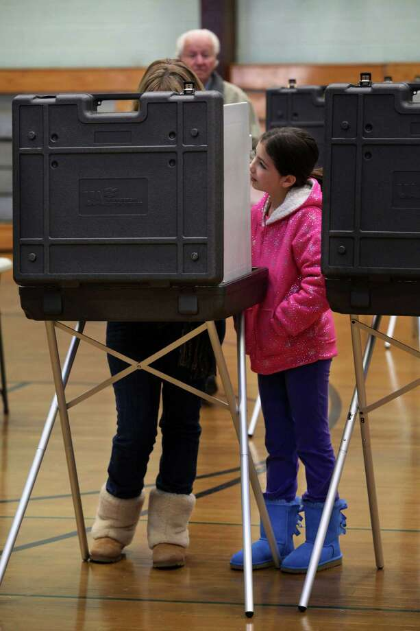 Brooke McFarland, 9, watches her mother, Elizabeth, vote at Hillcrest Middle School in Trumbull, Conn. on Tuesday, Nov. 5, 2013. Photo: BK Angeletti, B.K. Angeletti / Connecticut Post freelance B.K. Angeletti