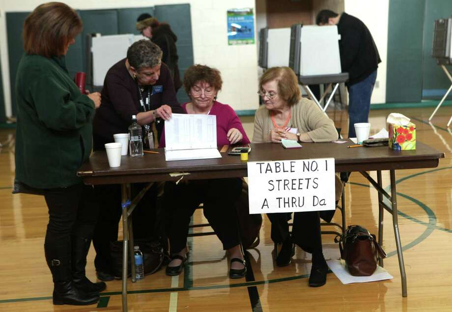Moderator Sylvia Brody, left behind table, assist checkers Linda Seyack, Center, and Ann Monaco, right, with a voter's address at Mohegan School in Shelton, Conn. on Tuesday, Nov. 5, 2013. Photo: BK Angeletti, B.K. Angeletti / Connecticut Post freelance B.K. Angeletti