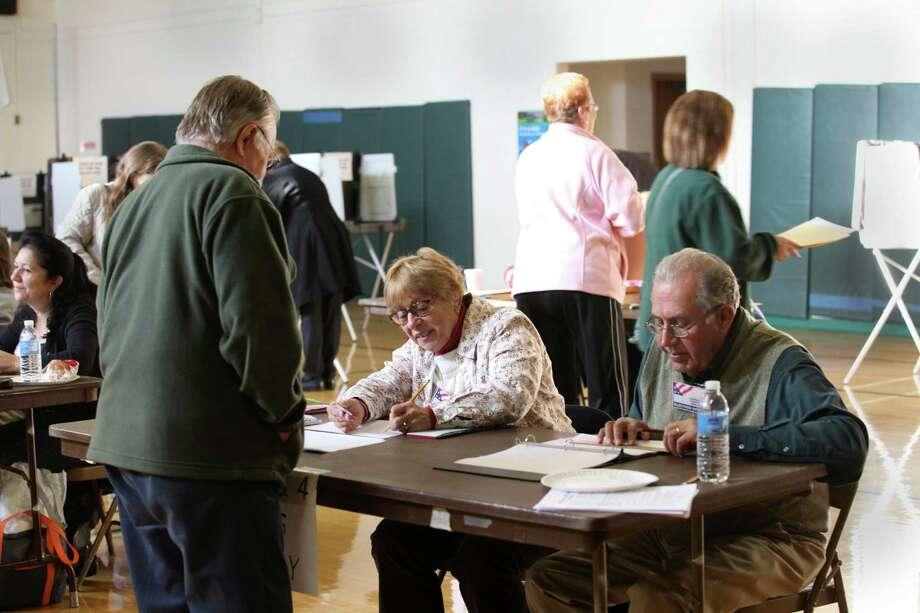 Joann and James Farnen check in voters at Mohegan School in Shelton, Conn. on Tuesday, Nov. 5, 2013. Photo: BK Angeletti, B.K. Angeletti / Connecticut Post freelance B.K. Angeletti