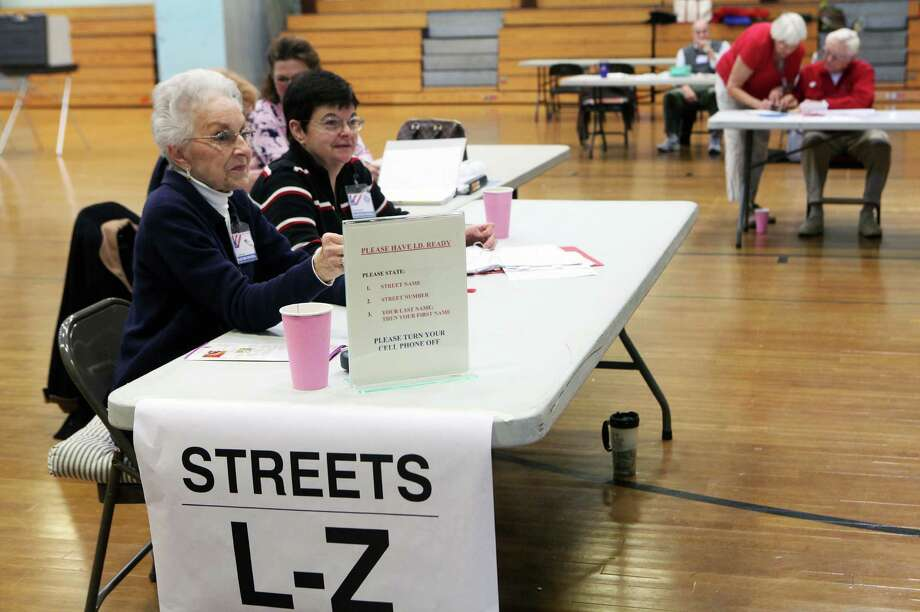 Checkers, Audrey Bajoros, left, and Teresa Garvey, assist voters at Hillcrest Middle School in Trumbull, Conn. on Tuesday, Nov. 5, 2013. Photo: BK Angeletti, B.K. Angeletti / Connecticut Post freelance B.K. Angeletti
